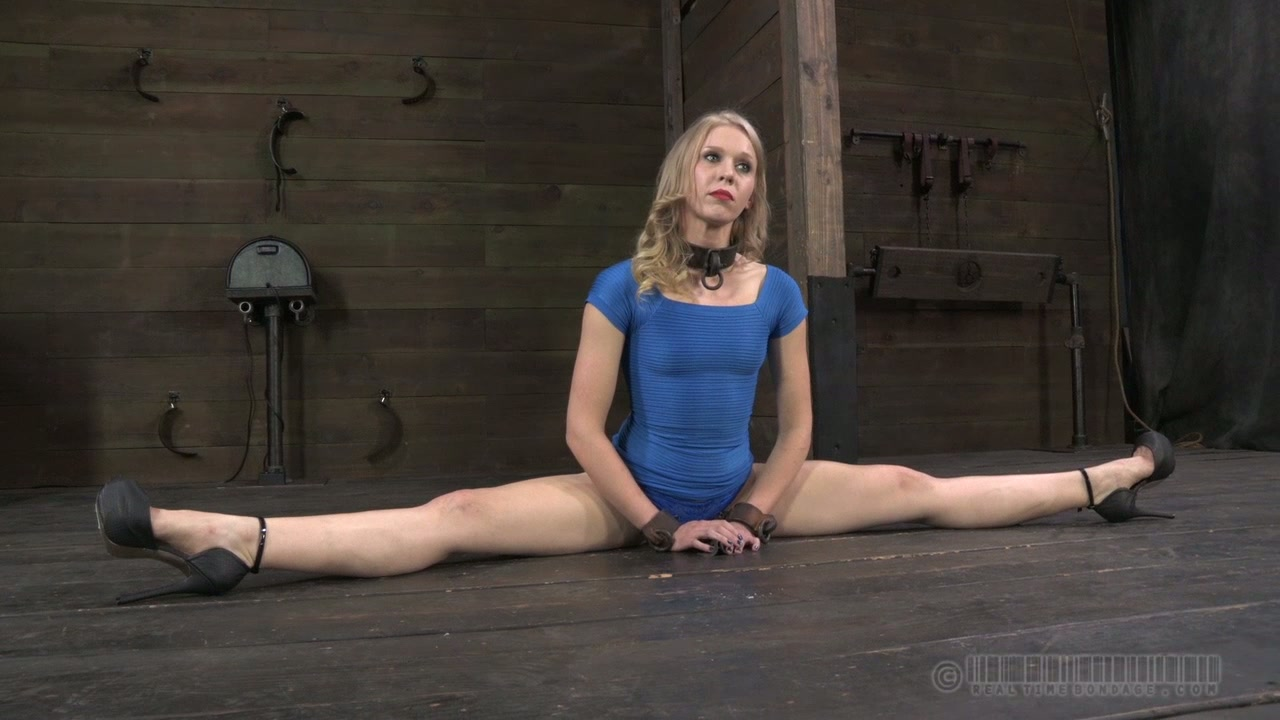 Skinny blond cutie sits on the floor with legs wide open in BDSM sex scene