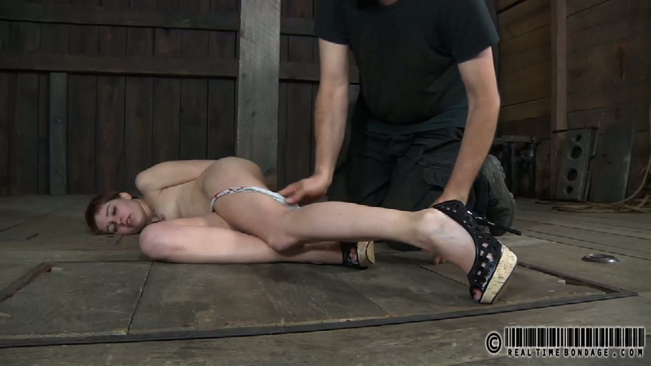 Skinny short haired doxy lies tied on the dirty floor in raunchy BDSM sex scene