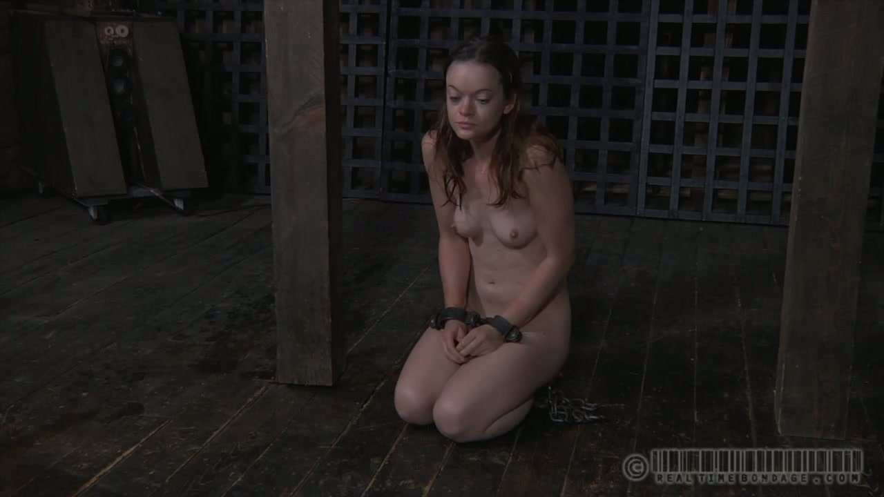 Slender brunette chick sits on dirty stinky floor naked in anticipation for BDSM tortures